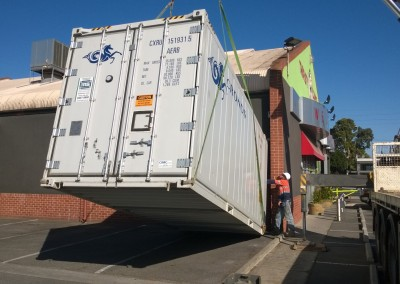 Refrigerated shipping container being lowered into convenient position for staff to access